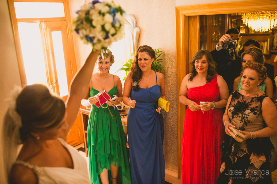 La novia saludando a sus amigas con el ramo levantado en una fotografía de boda en Martos