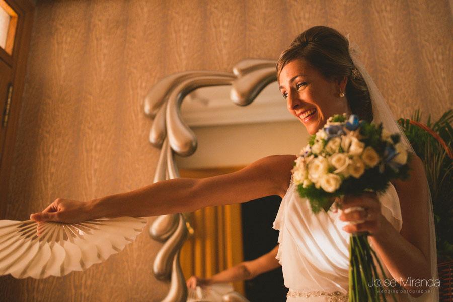 Mariah, la novia saludando a la gente que la espera en la calle para salir en una fotografía de boda en Martos