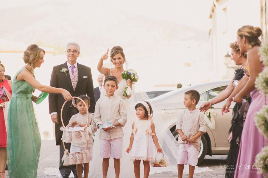 La novia con el padrino y los niños de arras entrando a la iglesia para su boda en una fotografía en Martos