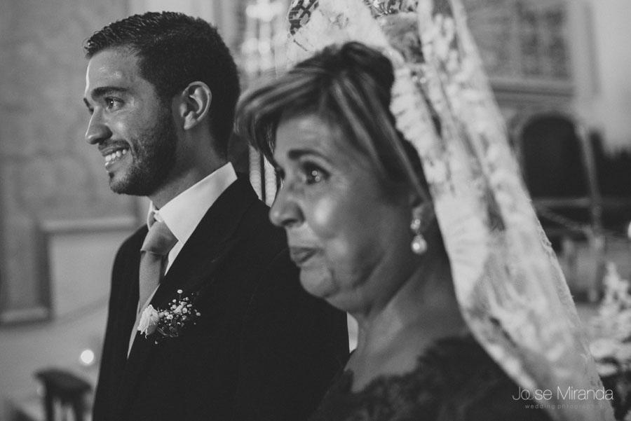 El novio y su madre emocionados viendo entrar a la novia en la iglesia