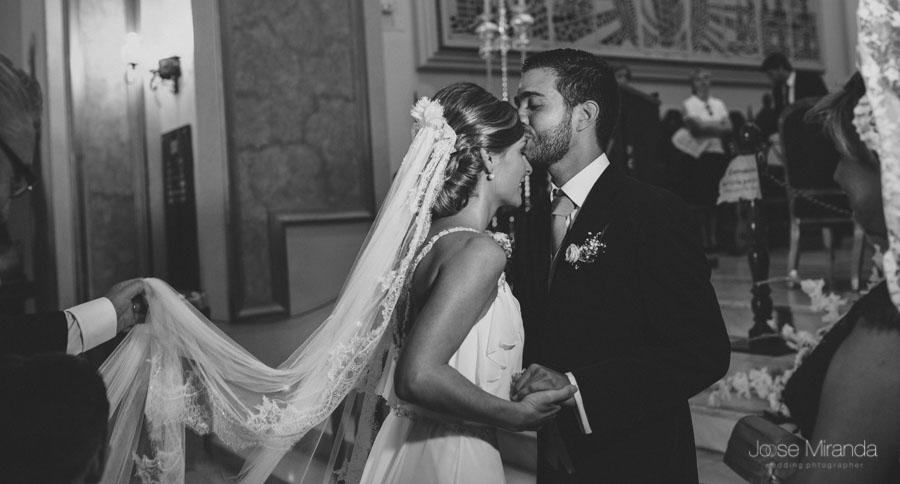 Curro, el novio, besando a Mariah, la novia, cuando está llegando al altar acompañados por sus padres