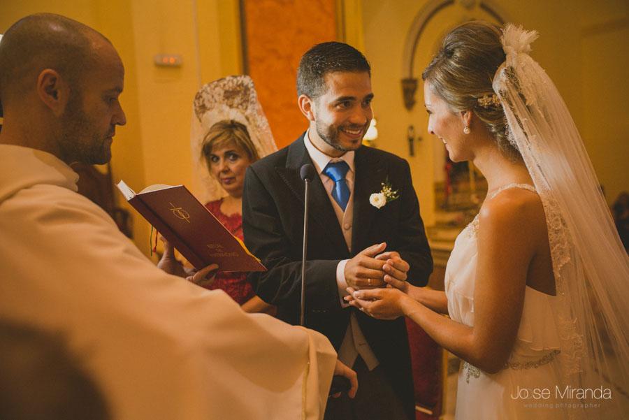 El novio riendo mientras le entrega las arras durante la ceremonia