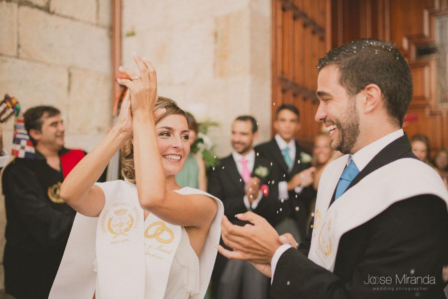 Los novios cantando y aplaudiendo a sus amigos tunos a la salida de la iglesia durante su boda en Martos