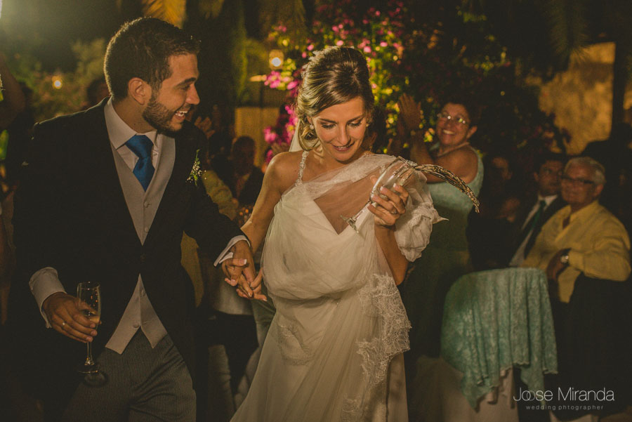 Novios brindando y calléndose el champan de la copa de la novia en una fotografía de boda de Jose Miranda
