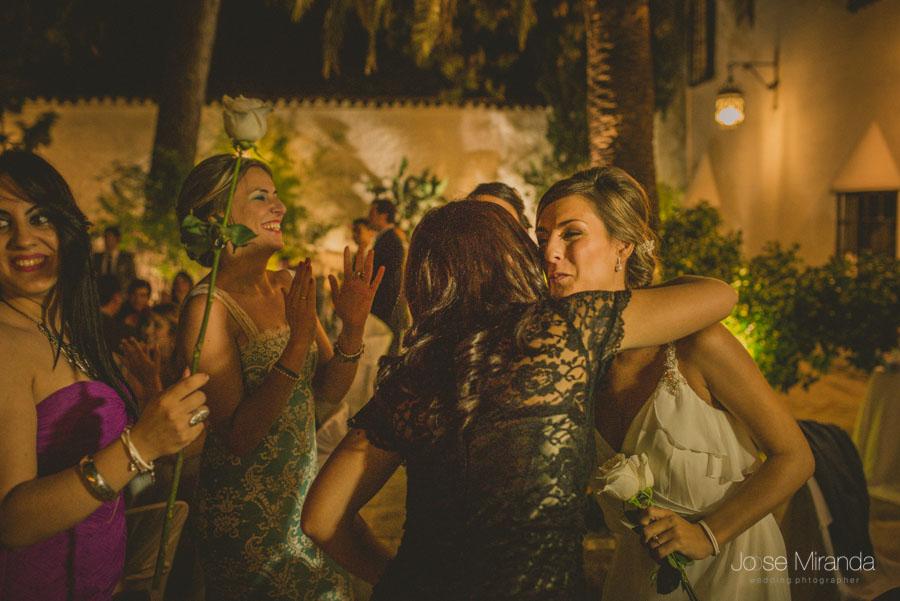 La novia repartiendo rosas entre sus amigas en una fotografía de boda en Martos de Jose Miranda