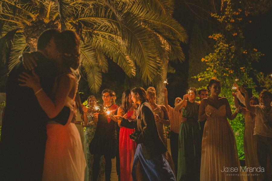 Invitados encendiendo las vengalas mientras los novios comienzan su baile