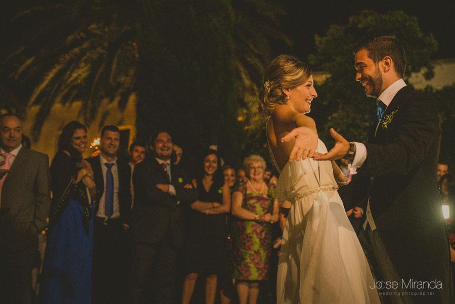 Novios bailando mientras sus invitados los miran sonrientes