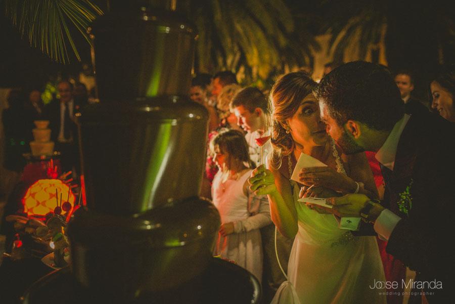 La novia con la fundee y mirando divertida al novio en una fotografía de boda en Martos