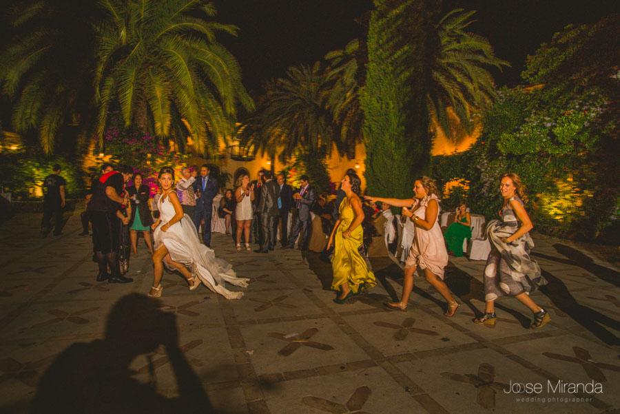 La novia corriendo durante el baile mientras sus amigas la persiguen