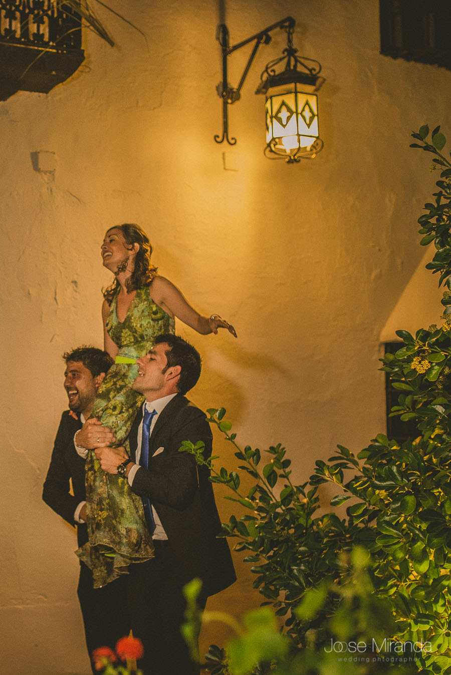 Los amigos subiendo a hombros a una amiga para ver a la novia entre los invitados
