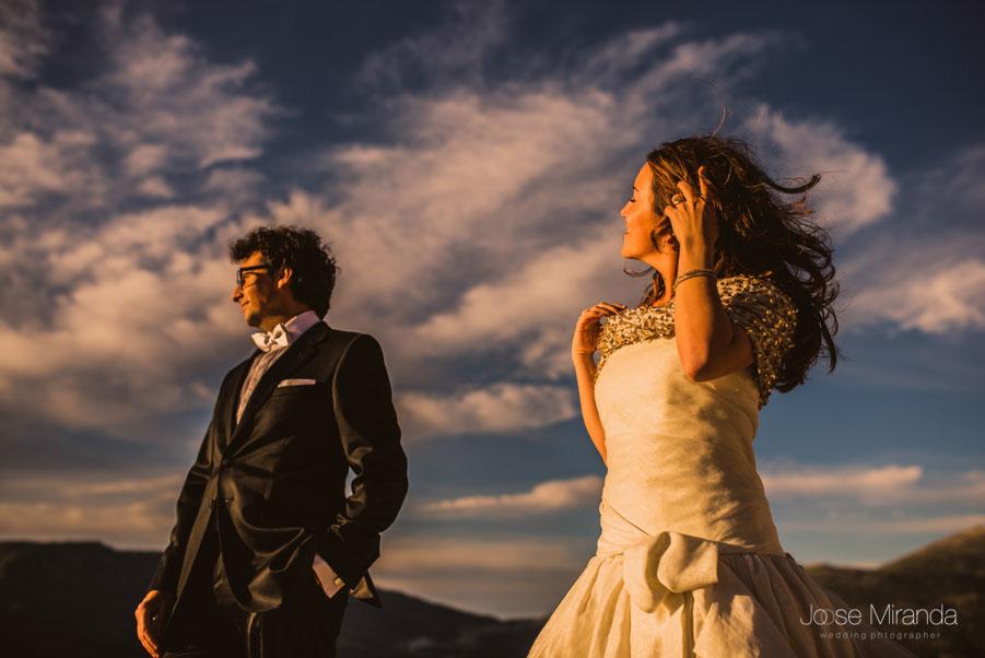 La novia arreglandose el pelo con el novio y el cielo con nubes detrás