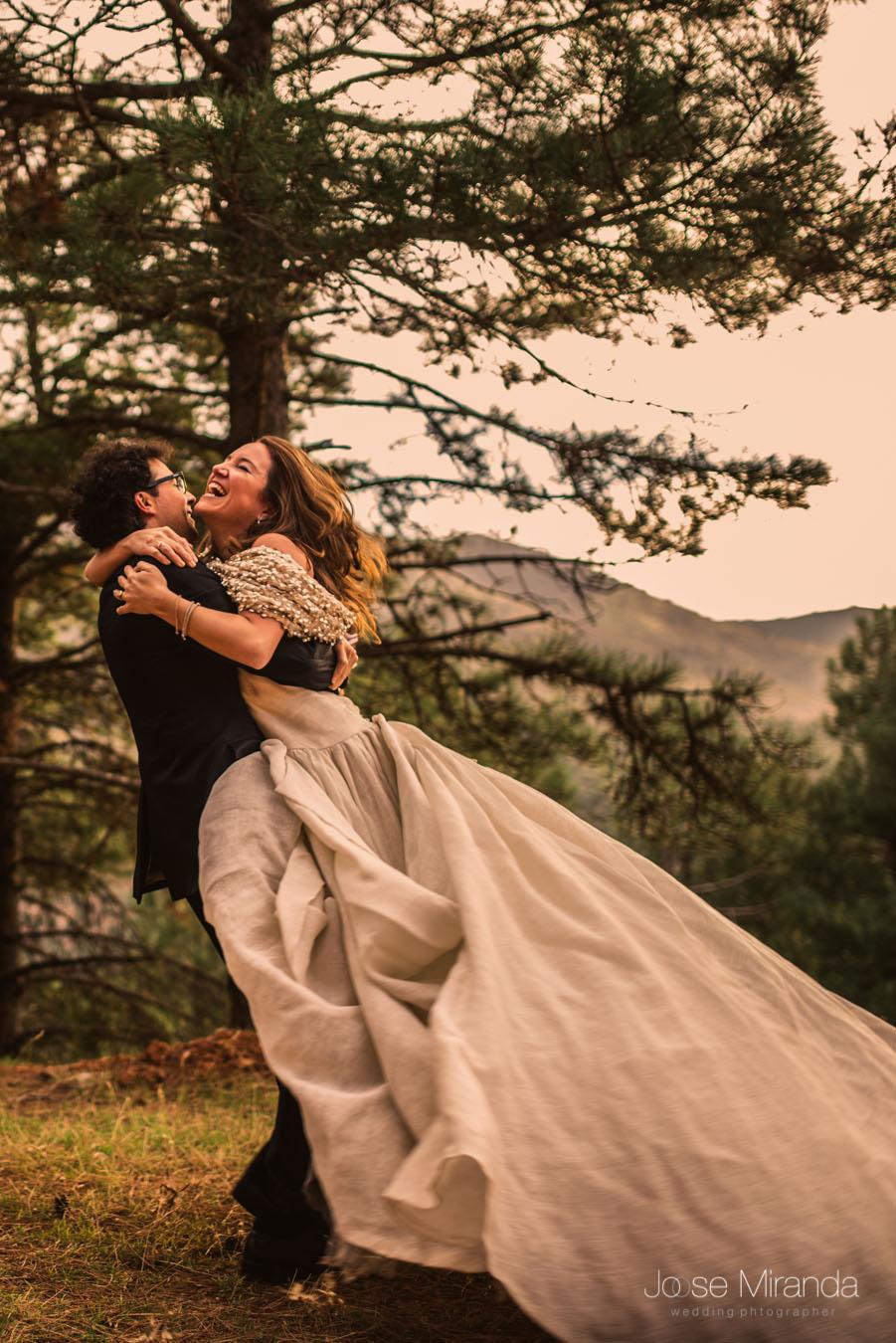 Novio cogiendo a la novia en brazos con el vestido volando