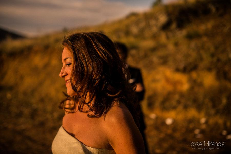 María con la cara soleada y el campo detrás.