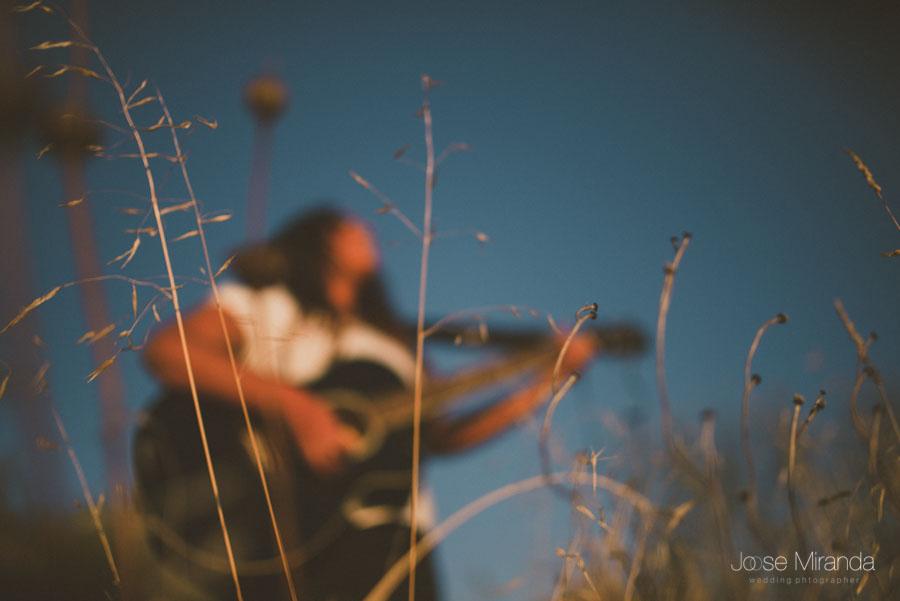 Chica tocando la guitarra en el campo