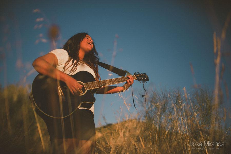 Cantante con guitarra en sesión fotográfica en el campo