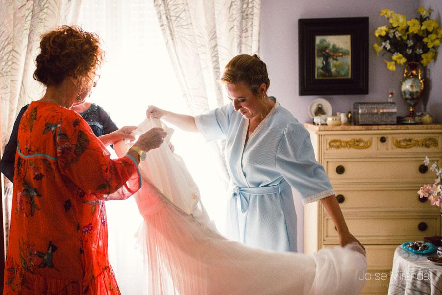 Novia descolgando el vestido para ponerselo en una imagen de Jose Miranda Fotografia