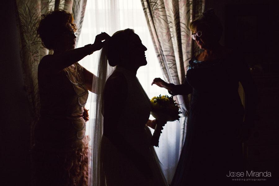 La madre y la amiga poniendo el velo a la novia