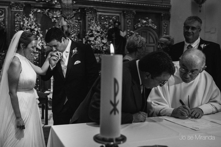 El novio besando la man de la novia mientras los familiares firman