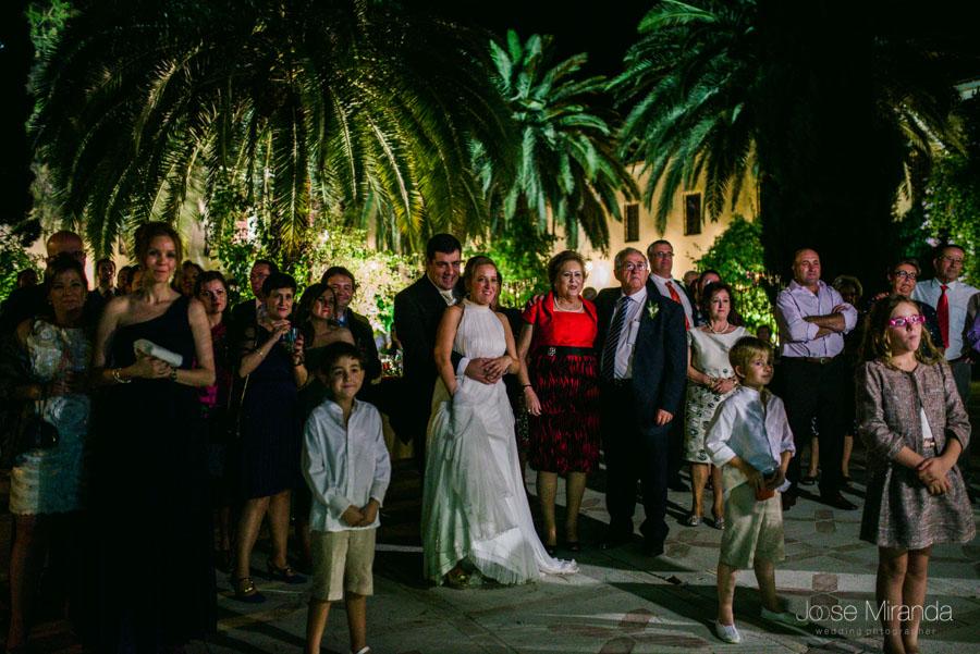Los novios y los invitados viendo el slide show de las fotografía de la boda