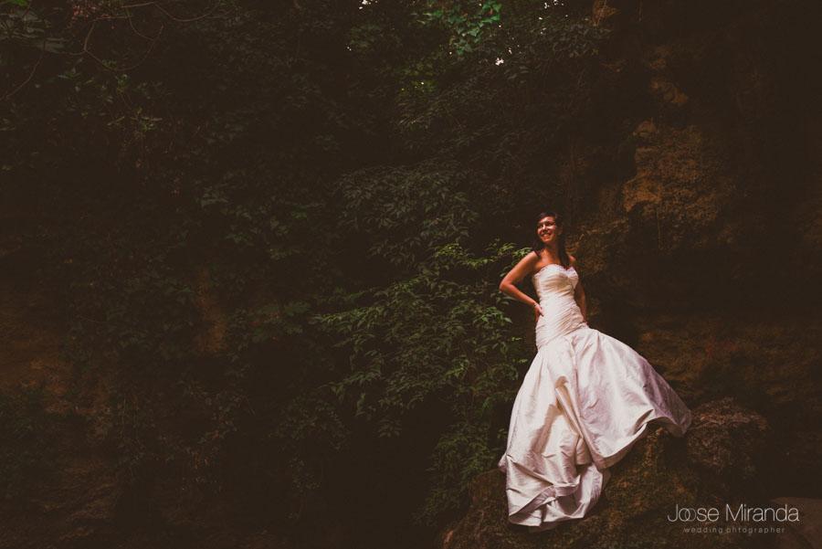Susana sobre una roca entre la vegetación del bosque en una fotografía de post boda de Jose Miranda Jaén Martos
