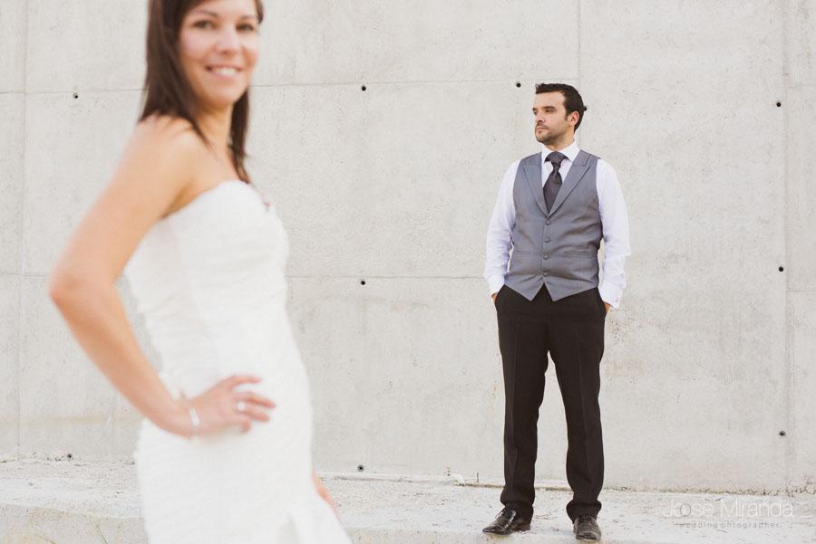 Marco enfocado sobre una pared de hormigón y Susana desenfocada en primer plano en una fotografía de post boda de Jose Miranda Jaén Martos