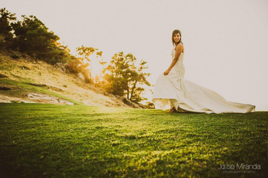Susana paseando su vestido por la hierba con la puesta de sol al fondo en una fotografía de post boda de Jose Miranda Jaén Martos