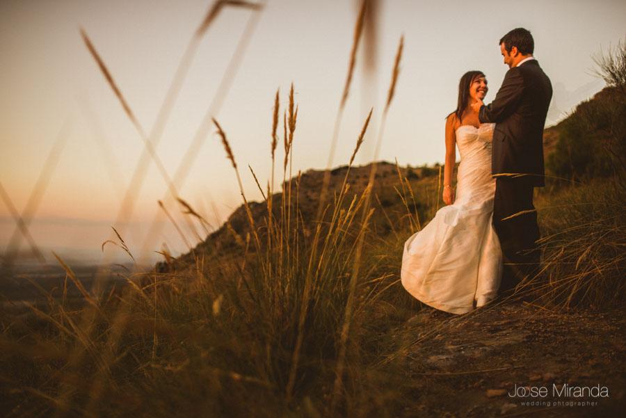 Susana y Marco entre las hierbas al atardecer en una fotografía de post boda de Jose Miranda Jaén Martos