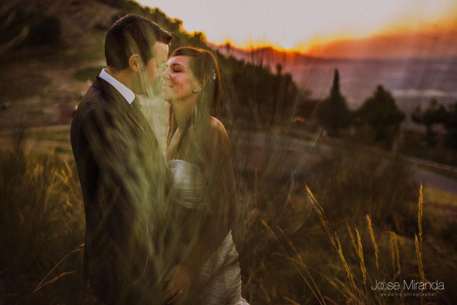 Susana y Marco a punto de besarse mientras el sol se pone en una fotografía de post boda de Jose Miranda Jaén Martos