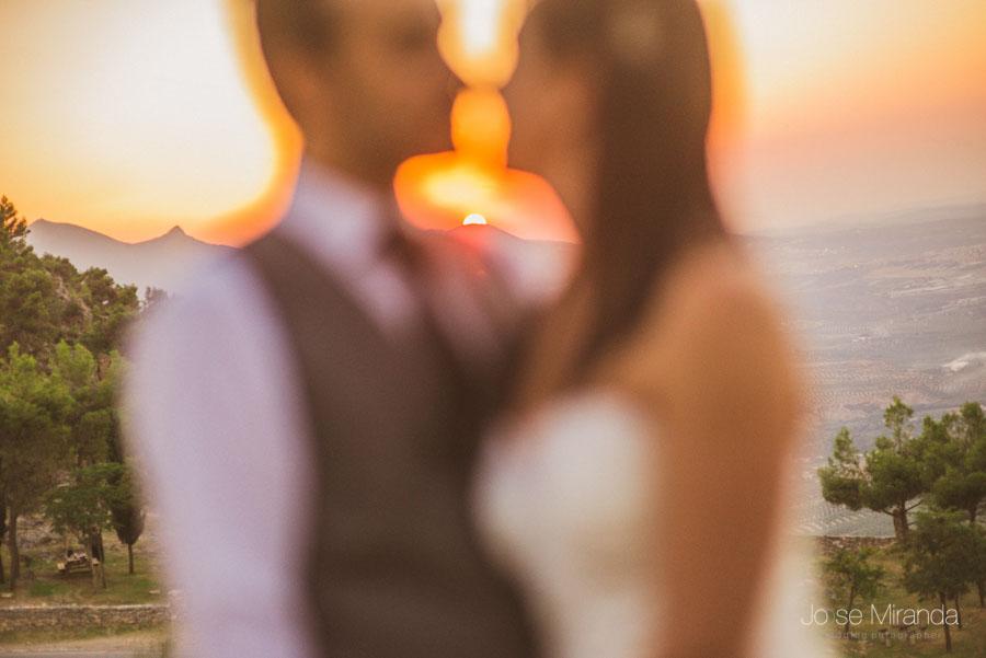 Susana y Marco en primer plano desenfocados mientras el sol se pone entre las maontañas en una fotgrafía de post boda
