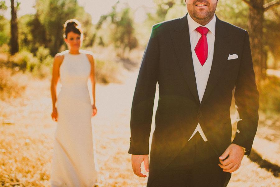 Novio enfocado con flare y la novia en segundo plano desenfocada